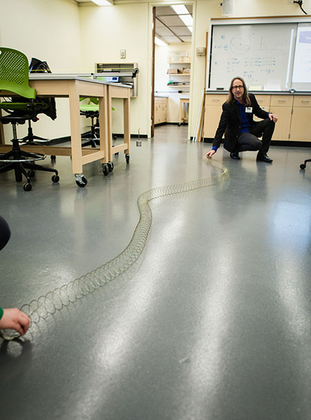 Photo of professor in lab with Slinky